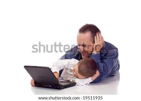 Cute little boy with his father laying on their stomach with a laptop
