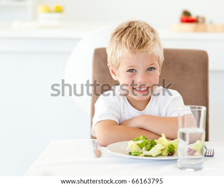 Cute little boy with his salad for lunch sitting at a table in the kitchen - stock photo