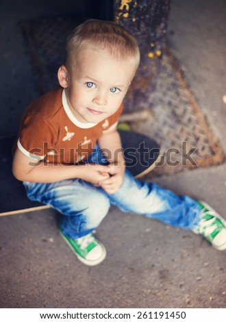 Cute little boy with his skateboard on a walk in the city