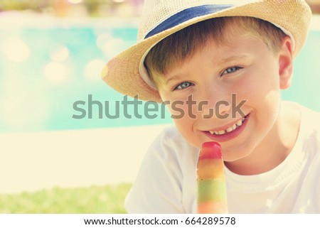 Cute little boy with ice cream next to the pool