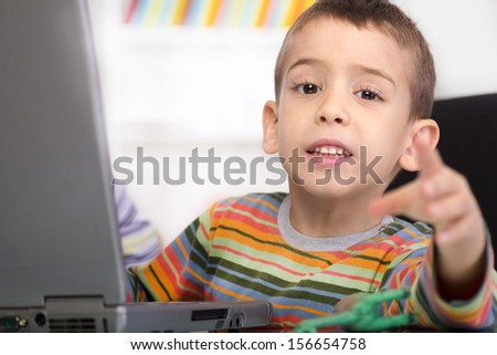 cute little boy with laptop shows