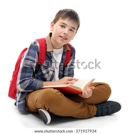 Cute little boy with red backpack reading a book, isolated on white