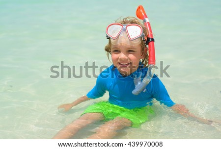 Cute little boy with snorkeling equipment at tropical beach
