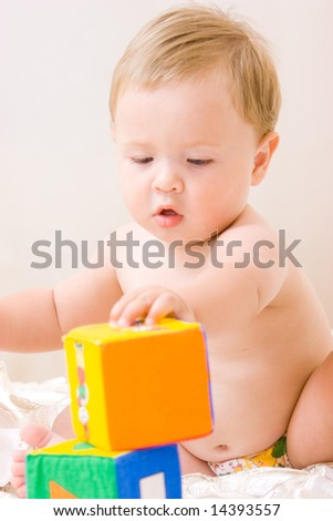Cute little boy with soft cubes toy - stock photo