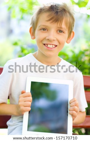 cute little boy with tablet computer outdoors - stock photo
