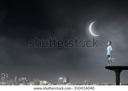 Cute little boy with toy bear in night darkness - stock photo
