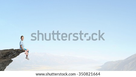 Cute little boy with toy bear on rock top - stock photo