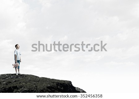 Cute little boy with toy bear on rock top