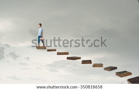 Cute little boy with toy bear walking on ladder of books - stock photo
