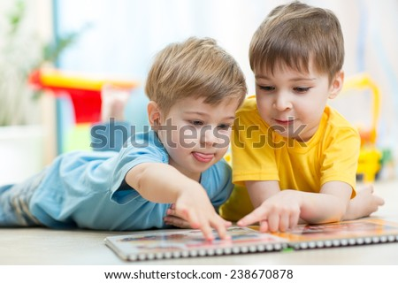 Cute little boys at home reading a book - stock photo