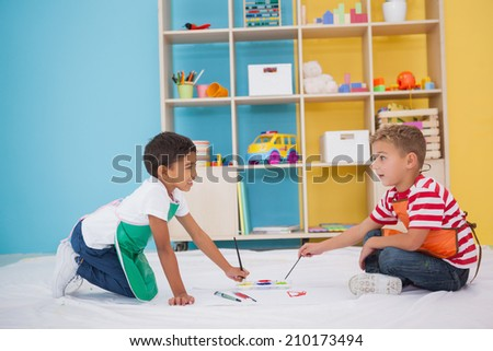 Cute little boys painting on floor in classroom at the nursery school - stock photo