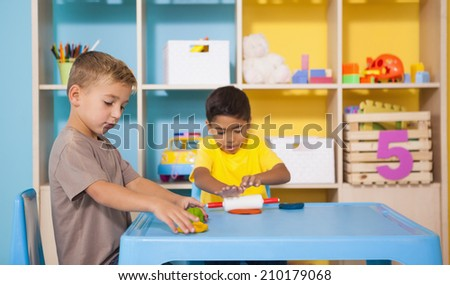 Cute little boys playing with modelling clay in classroom at the nursery school - stock photo