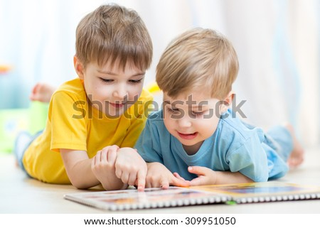 cute little boys read book together on floor at home - stock photo