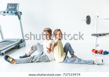 cute little boys showing thumbs up and smiling at camera in gym