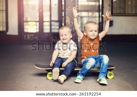 Cute little boys sitting on a skateboard on their walk in the city - stock photo