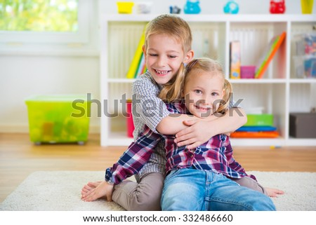 Cute little brother and sister having fun at home - stock photo