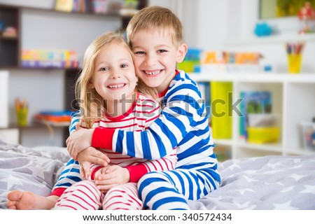 Cute little brother and sister in pajamas at home