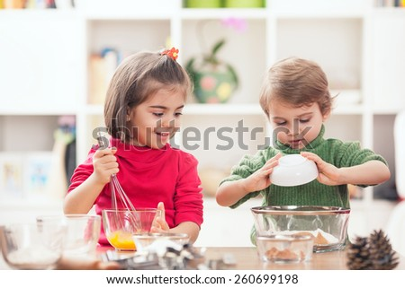Cute little brother and sister preparing a dough standing in the kitchen - stock photo