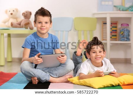 Cute little brothers using gadgets on the floor at home