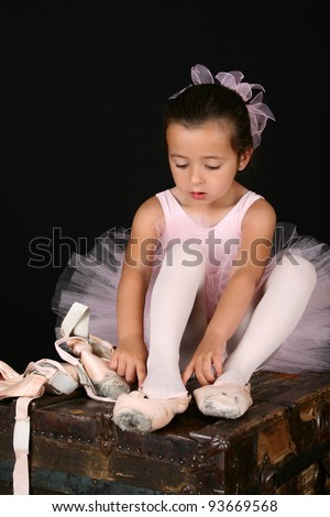 Cute little brunette girl trying on ballet pointe shoes - stock photo