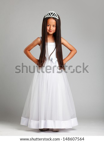 Cute little brunette in elegant dress and crown - stock photo