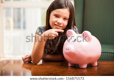 Cute little brunette pointing at her piggy bank with some copy space on the side
