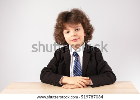 Cute little businessman sitting at his desk with a smile looking at the camera. Gray background.