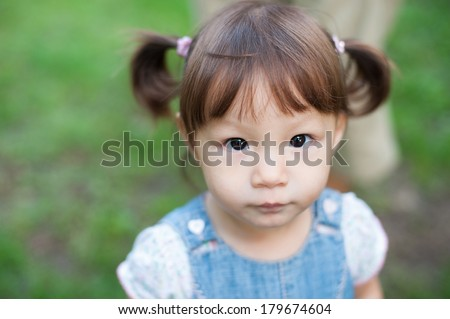 Cute little Caucasian/Asian/Eurasian girl is looking at the camera. - stock photo