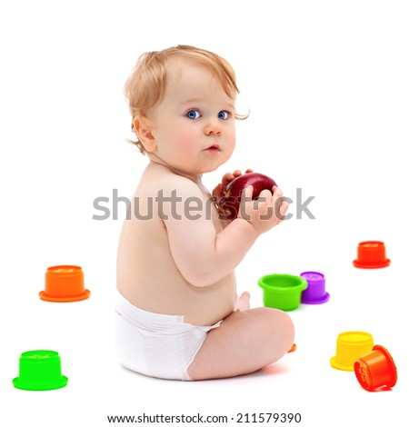 Cute little caucasian boy 11 months old sits and eats red apple on white background
