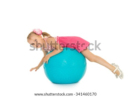Cute little Caucasian girl in a short pink dress riding a Big blue ball for fitness-Isolated on white background