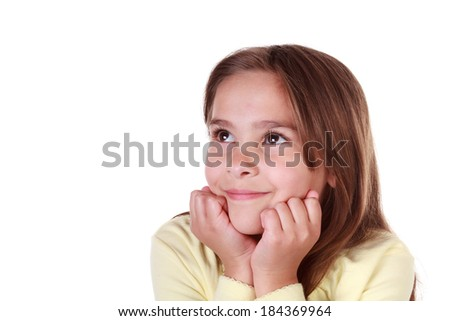 Cute little Caucasian girl with brown hair in a yellow outfit looking up and smiling with her hands on chin on an isolated white background with room for copy - stock photo