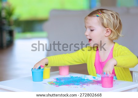 Cute little child, blonde artistic toddler girl painting with colorful finger paints indoors at bright room at home or kindergarten  - stock photo