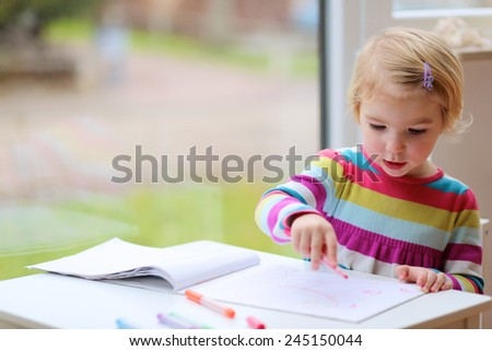 Cute little child, blonde preschooler girl is drawing with felt-tip pens at home or kindergarten sitting at small table next to window - stock photo