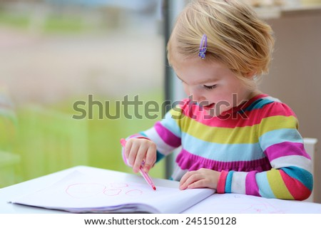 Cute little child, blonde preschooler girl is drawing with felt-tip pens at home or kindergarten sitting at small table next to window