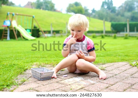 Cute little child, blonde toddler girl playing outdoors sitting at terrace at the backyard of the house drawing or painting with colorful chalk. Big green garden at the background. - stock photo