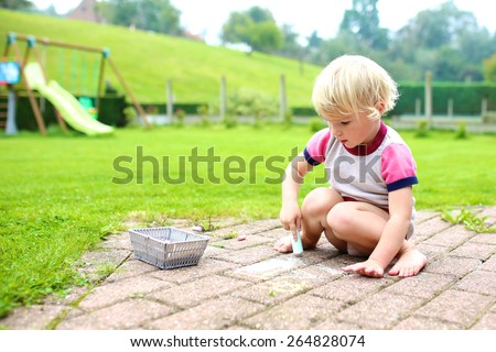 Cute little child, blonde toddler girl playing outdoors sitting at terrace at the backyard of the house drawing or painting with colorful chalk. Big green garden at the background - stock photo