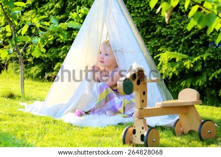 Cute little child, blonde toddler girl, wearing beautiful dress enjoying summertime playing outdoors in the garden hiding in home-made tent on a sunny day - stock photo