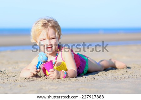 Cute little child, blonde toddler girl wearing colorful necklace and swimsuit playing with plastic ice cream cone toy lying on sandy beach at North Sea - stock photo