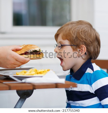 Cute little child eating fast food: french fries and hamburger in cafe. Square format. - stock photo
