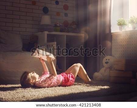 Cute little child girl reading a book. - stock photo