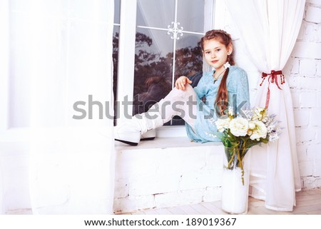 Cute little child girl with spring flowers, happy baby girl with basket of flowers.
