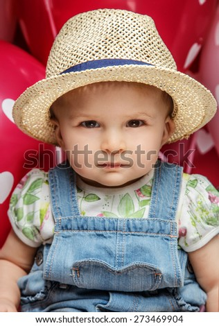 Cute little child in jeans costume and summer hat. Balloons background - stock photo