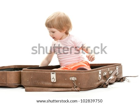 Cute little child inside a big suitcase, studio shot on white background