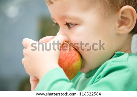 Cute little child is biting red apple and smile while sitting at table, isolated over white - stock photo