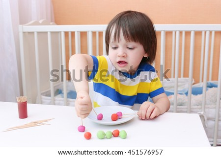 Cute little child made lollipops of playdough and toothpicks at home