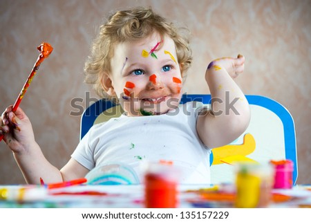 Cute little child painting with colorful paints