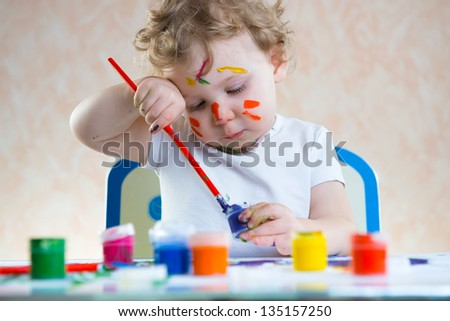Cute little child painting with colorful paints - stock photo