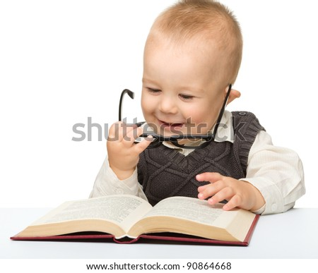 Cute little child play with book and glasses while sitting at table, isolated over white - stock photo