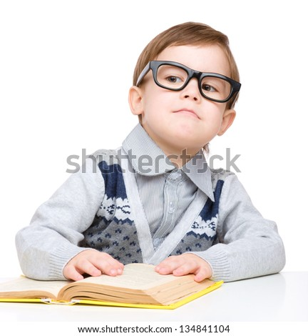 Cute little child play with book and wearing glasses while sitting at table, isolated over white