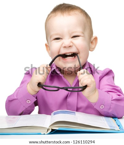 Cute little child play with book while sitting at table and biting glasses, isolated over white - stock photo